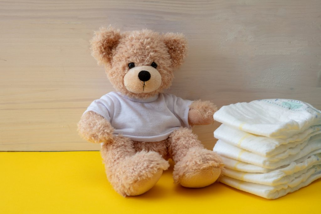 Baby diapers and teddy on yellow color floor